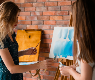 Photograph of two women painting.