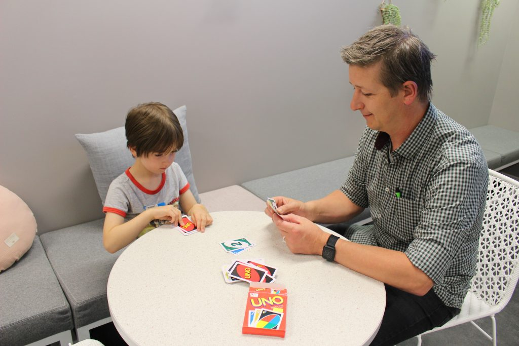 Photo of Adam playing Uno with his son August.