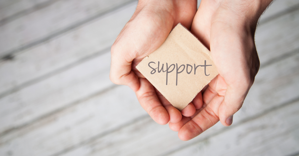 Photo of a hand cupping a small sign that says support.