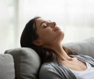 A photo of a woman relaxing on a couch practicing mindful breathing exercises